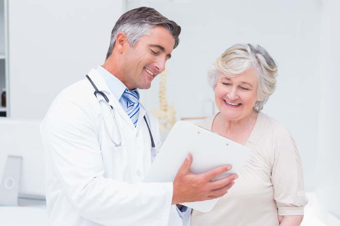 Happy doctor and patient discussing over reports in clinic